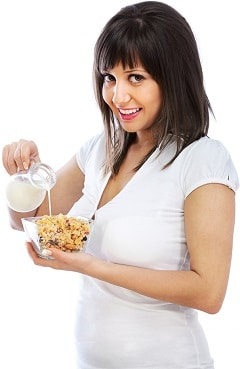 smiling brunette pouring milk on cereal